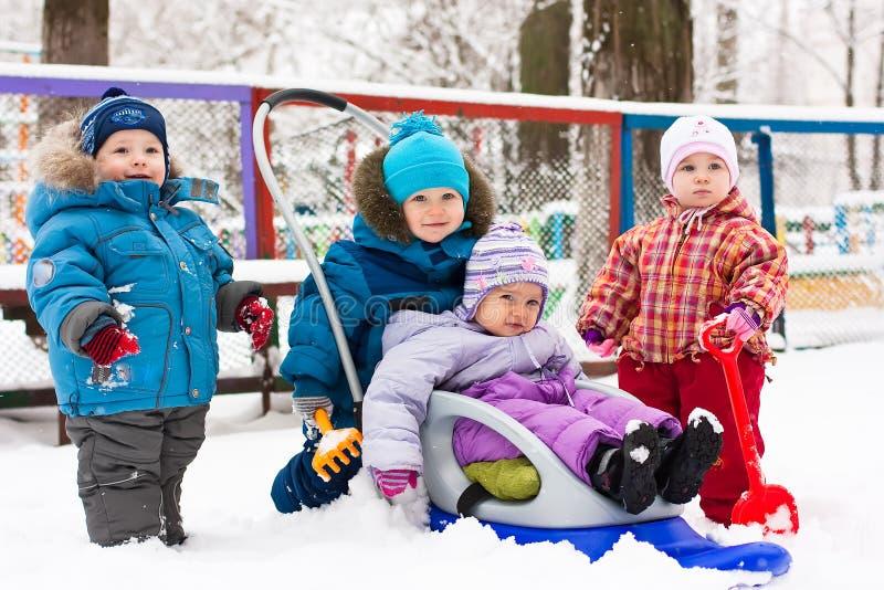 Kinder, die im Schnee im Freien spielen stockbilder