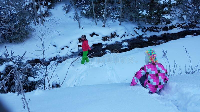 Kinder, die im Winterschnee durch Fluss spielen stockbild
