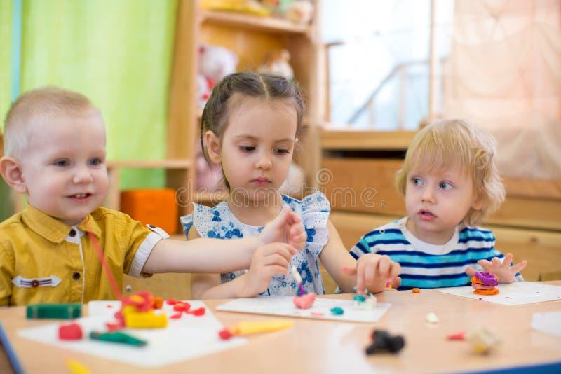 Kinder, die Künste und Handwerk im Tagesbetreuungskindergarten tun stockbild