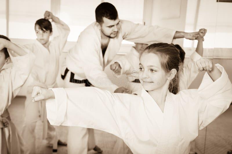 Kinder, die Kriegsbewegungen in der Karateklasse versuchen stockbild