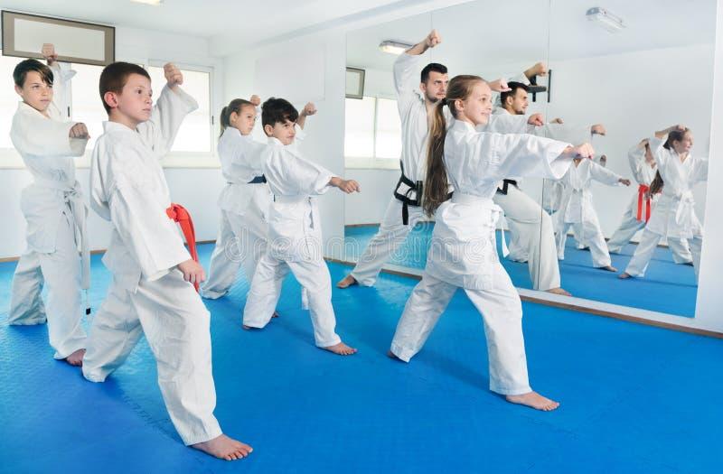 Kinder, die Kriegsbewegungen in der Karateklasse versuchen stockfotos