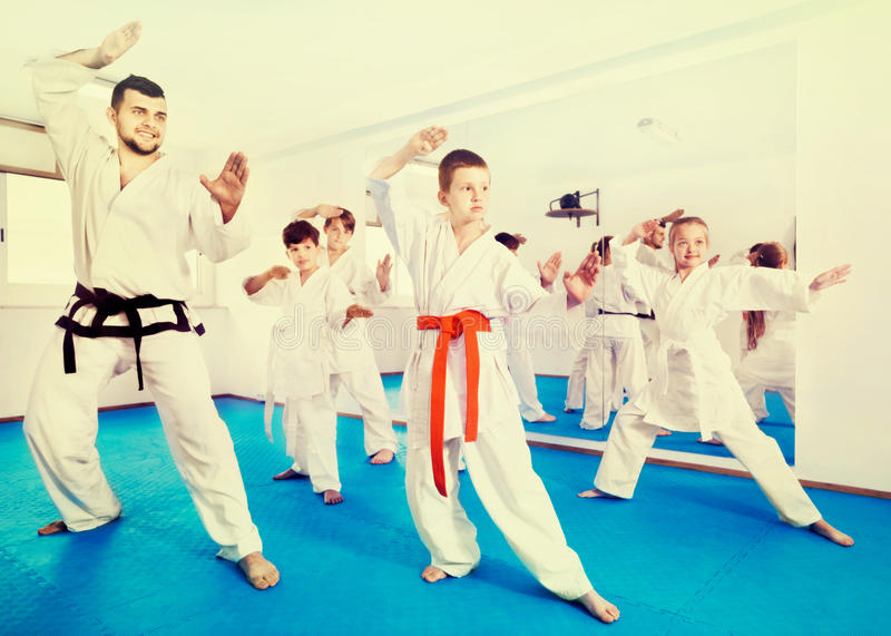 Kinder, die Kriegsbewegungen in der Karateklasse versuchen lizenzfreie stockfotos