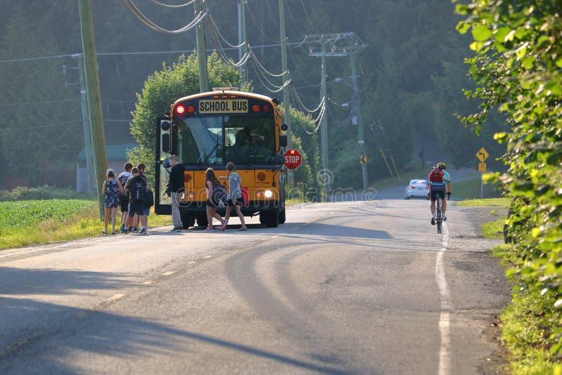 Kinder, die ländlichen Schulbus verschalen lizenzfreie stockfotografie