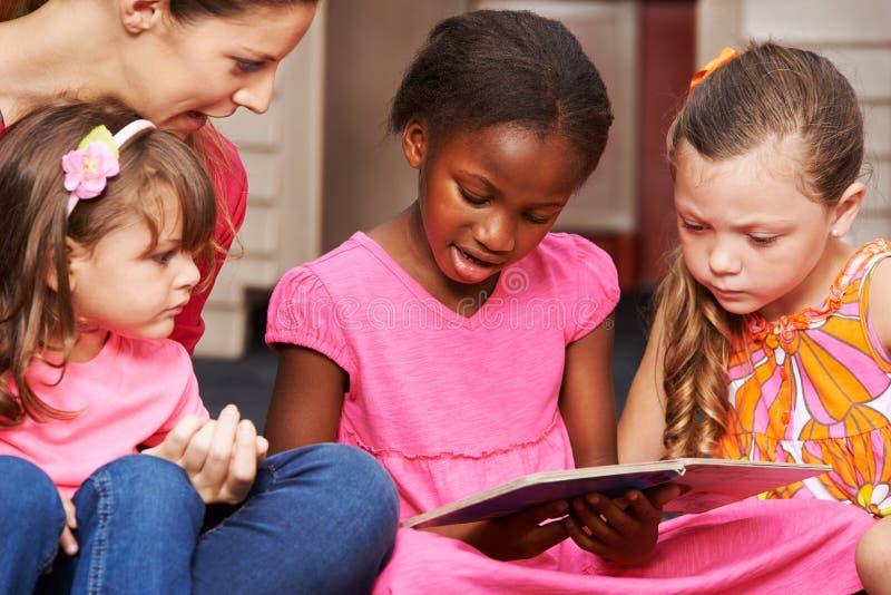 Kinder, die lernen, mit Kindergärtnerin zu lesen lizenzfreies stockbild