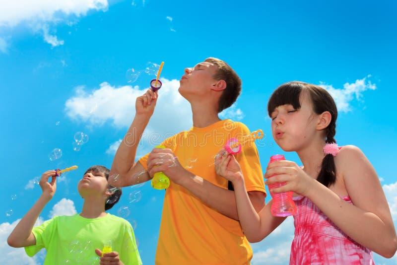 Kinder, die Luftblasen durchbrennen lizenzfreie stockfotos