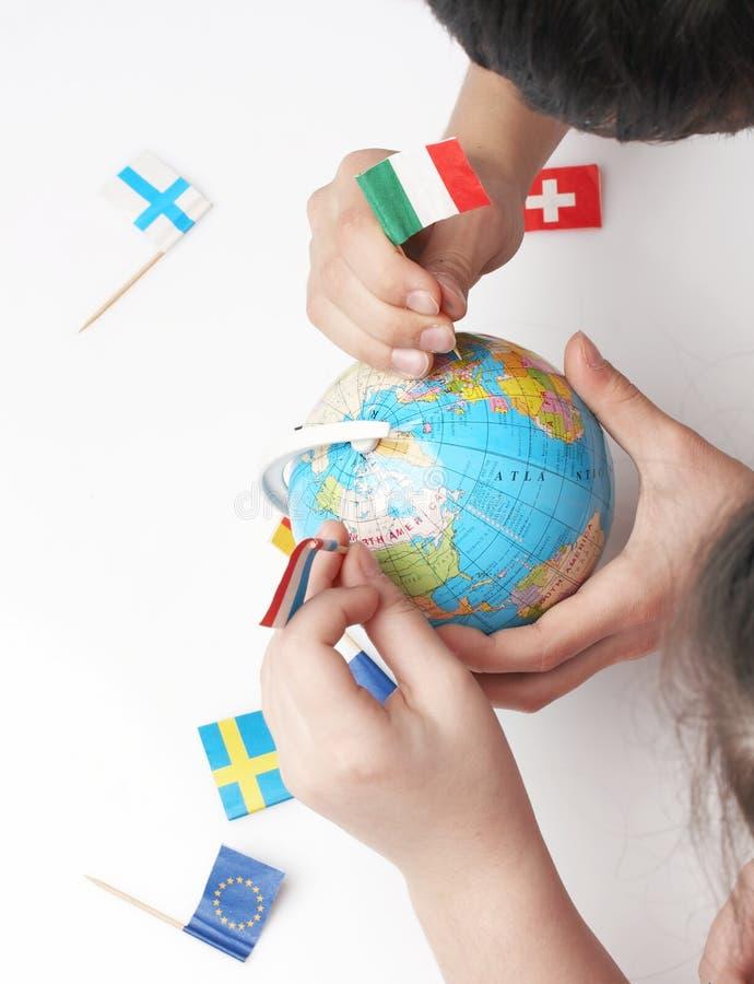 Kinder, die Markierungsfahnen auf Weltkugel zeigen stockfoto