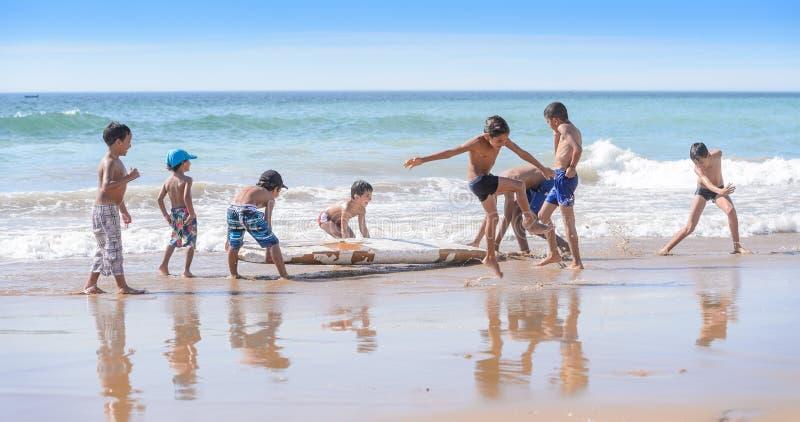 Kinder, die mit altem Surfbrett, Taghazout-Brandungsdorf, Agadir, Marokko spielen stockbilder