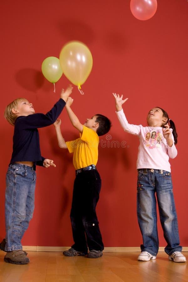 Kinder, die mit Ballons spielen lizenzfreie stockbilder