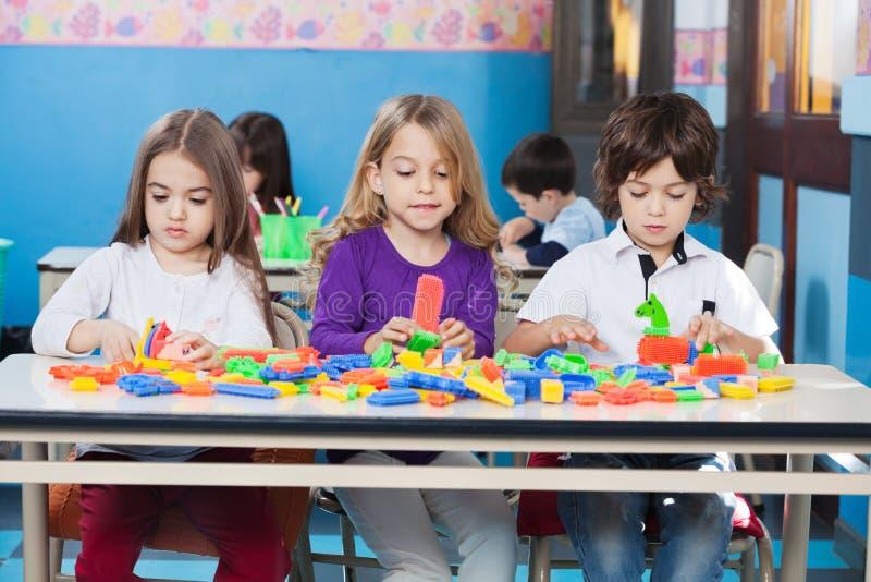 Kinder, die mit Bau-Blöcken herein spielen lizenzfreie stockfotos
