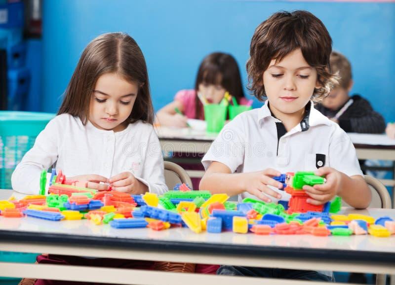 Kinder, die mit Bau-Blöcken herein spielen lizenzfreie stockfotografie
