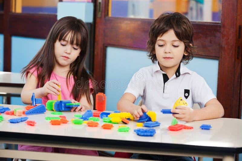 Kinder, die mit Bau-Blöcken am Schreibtisch spielen stockfotos