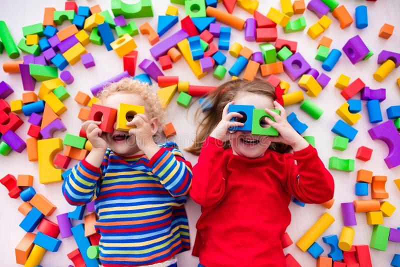 Kinder, die mit bunten Blöcken spielen lizenzfreie stockfotografie