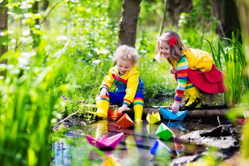 Kinder, die mit bunten Papierbooten in einem Park spielen stockbilder