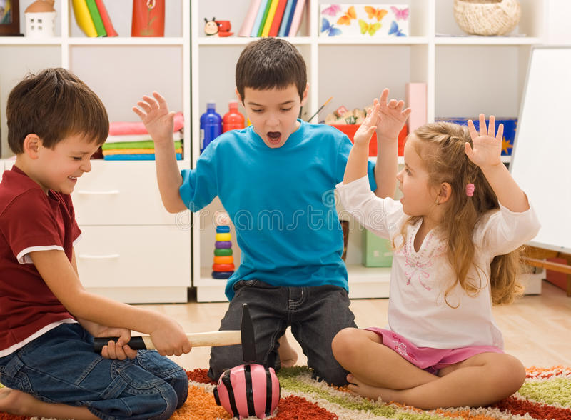 Kinder, die mit einem piggybank spielen lizenzfreie stockbilder