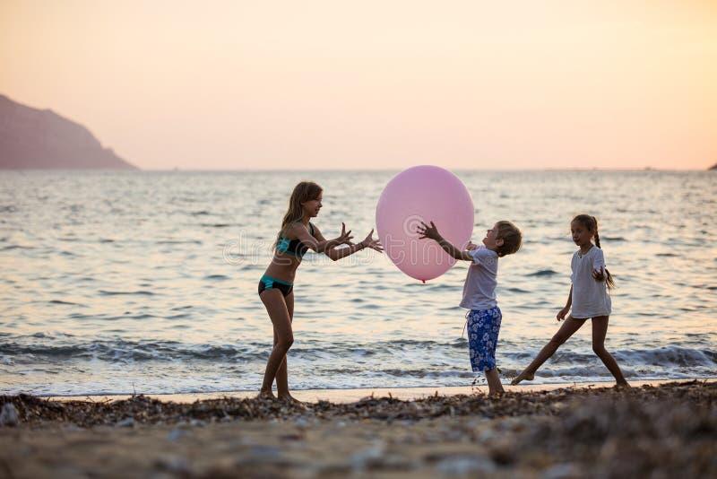 Kinder, die mit enormem rosa Ballon auf Strand spielen stockfotografie