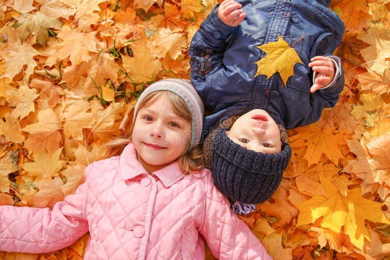 Kinder, die mit Herbst gefallenen Blättern im Park spielen stockfoto