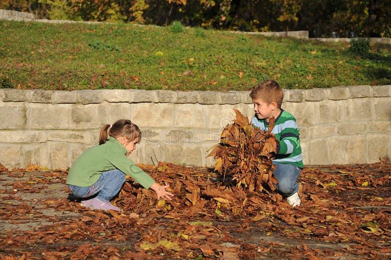 Kinder, die mit Herbst gefallenen Blättern im Park spielen lizenzfreies stockfoto