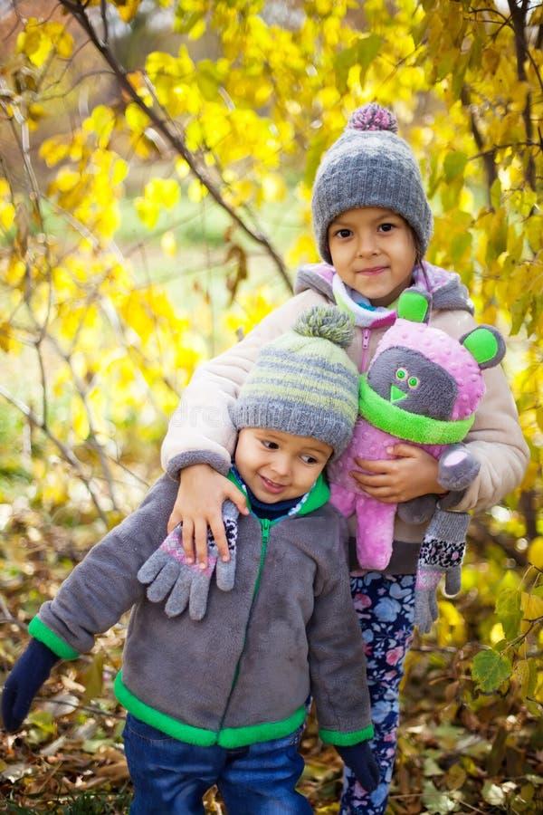 Kinder, die mit Herbst gefallenen Blättern im Park spielen lizenzfreies stockbild