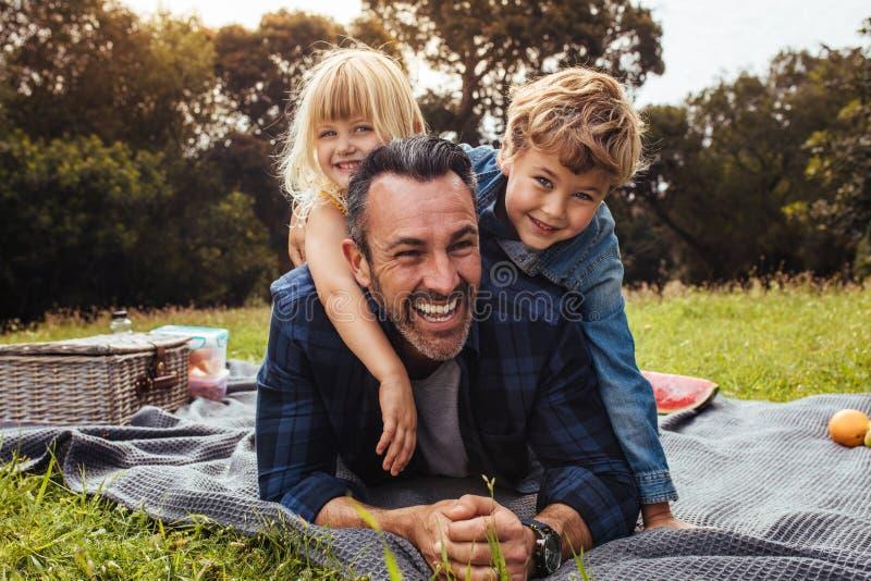 Kinder, die mit ihrem Vater auf Picknick spielen lizenzfreie stockfotos