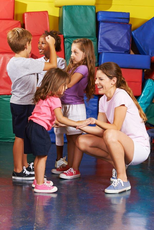 Kinder, die mit Kindergärtnerin in der Turnhalle trainieren stockbild