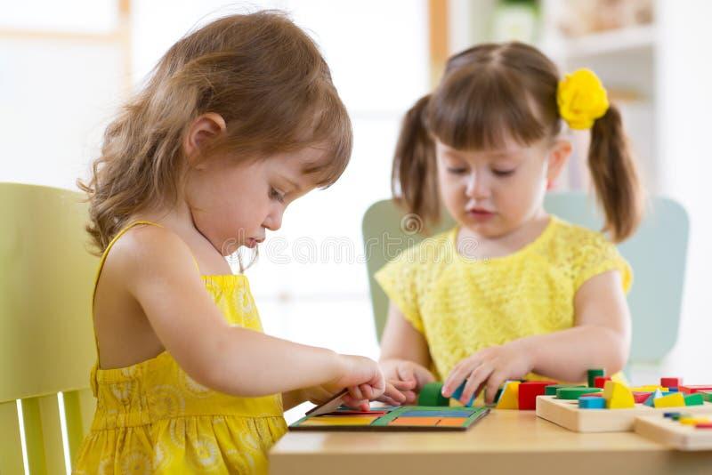 Kinder, die mit logischem Spielzeug auf Schreibtisch im Kindertagesstättenraum oder -kindergarten spielen Kinder, die Formen, Far stockfoto