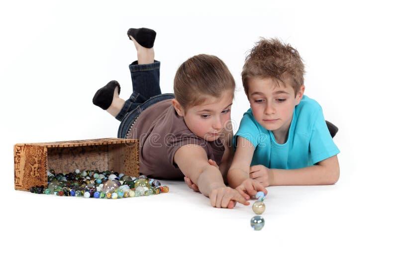 Kinder, die mit Marmoren spielen stockfoto