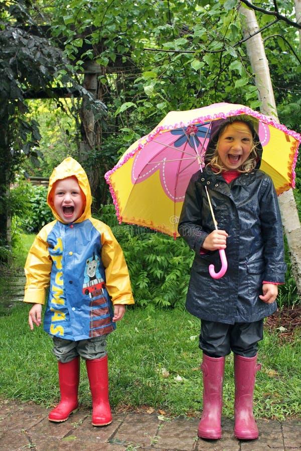 Kinder, die mit Regenschirm im Regen lachen stockbilder