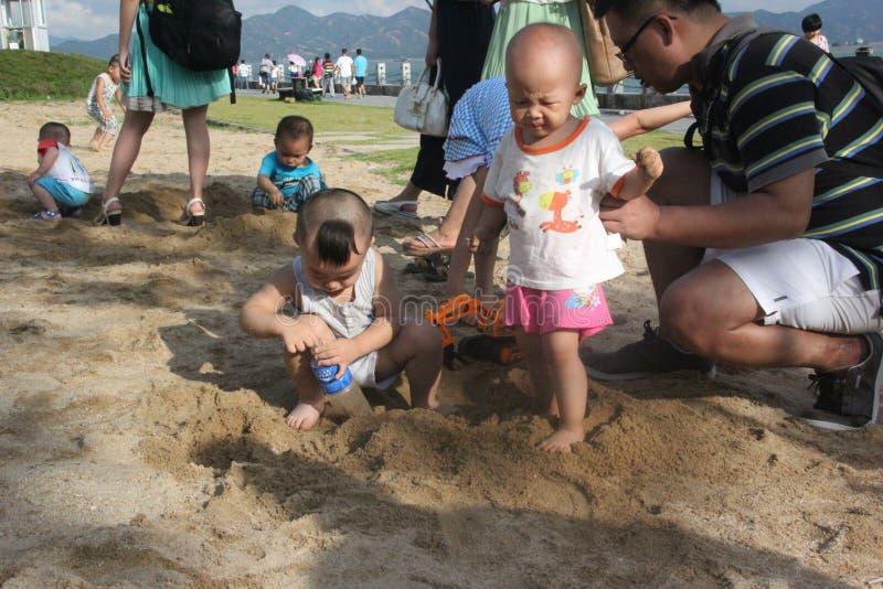 Kinder, die mit Sand spielen lizenzfreie stockfotografie
