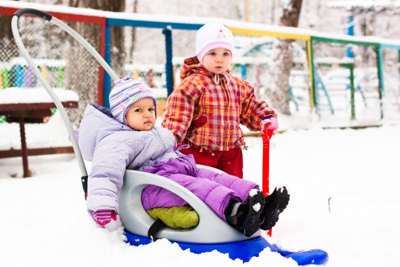 Kinder, die mit Schlitten und Spaten im Schnee spielen stockfoto
