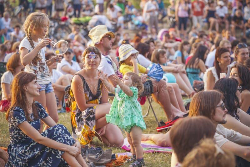 Kinder, die mit Seifenblasen während eines Konzerts von klassischem spielen lizenzfreies stockfoto