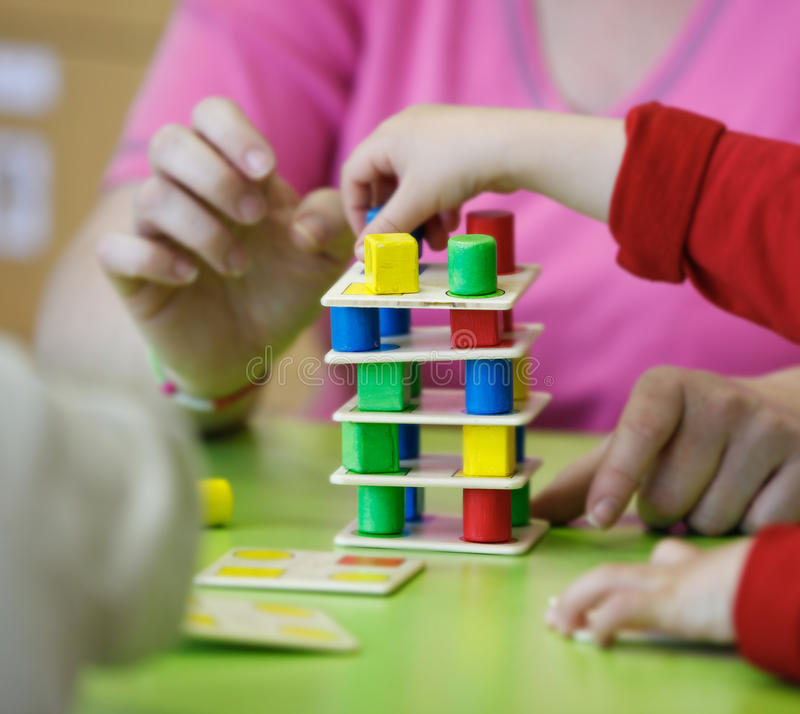 Kinder, die mit selbst gemachten pädagogischen Spielwaren spielen stockbild