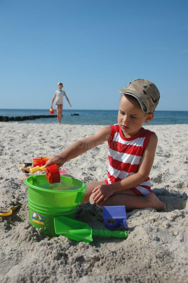 Kinder, die mit Spielwaren auf dem Strand spielen lizenzfreies stockfoto