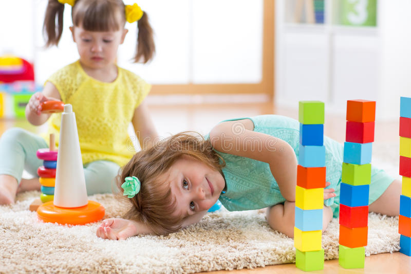 Kinder, die mit Spielwaren im Kindergarten spielen lizenzfreie stockfotografie