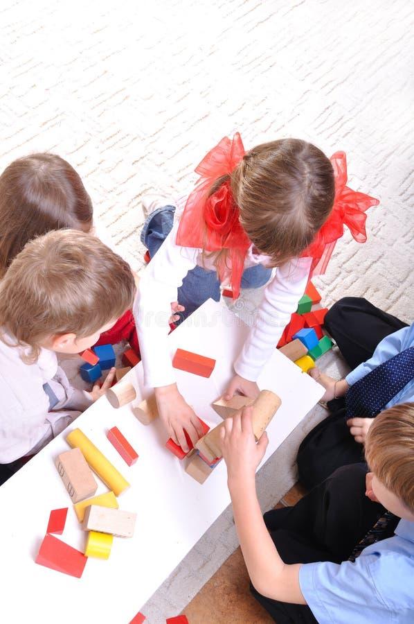 Kinder, die mit Spielzeugblöcken spielen stockbilder