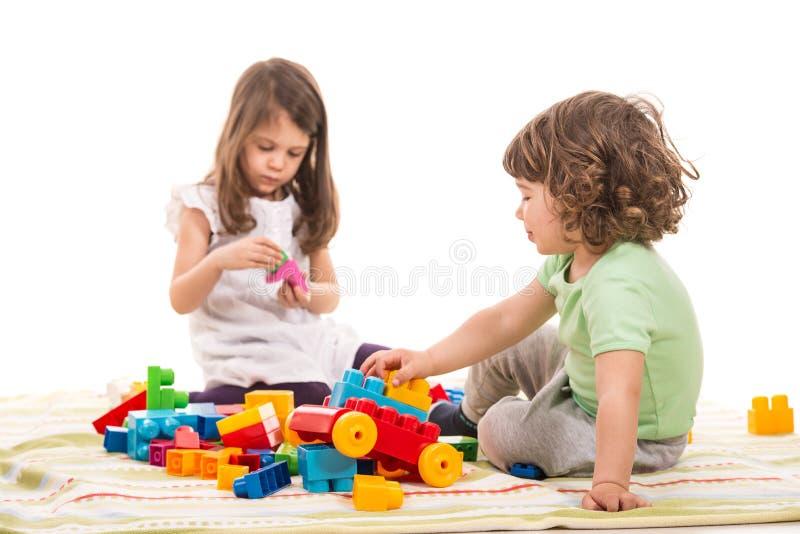 Kinder, die mit Ziegelsteinspielwaren spielen stockbild