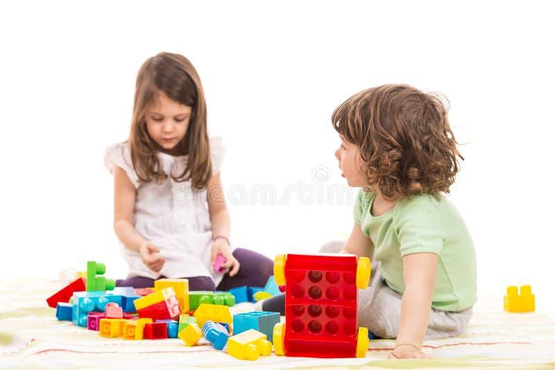 Kinder, die mit Ziegelsteinspielwaren spielen stockbilder