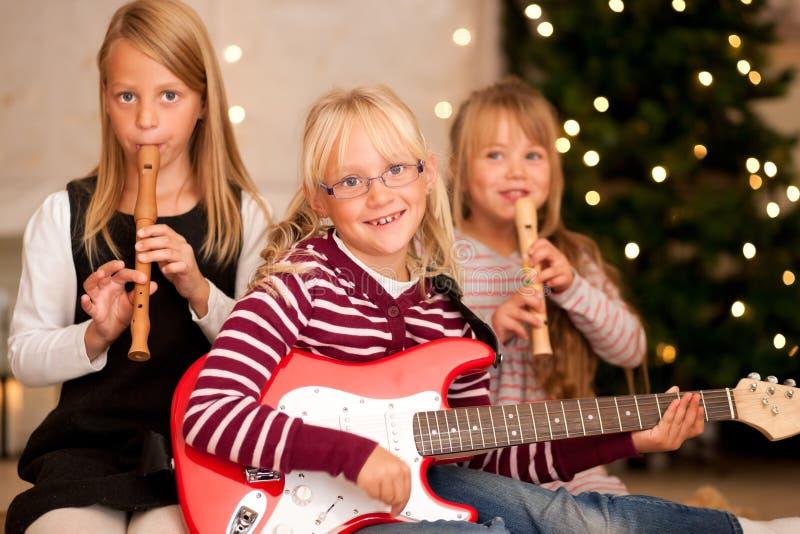 Kinder, die Musik für Weihnachten bilden stockbilder