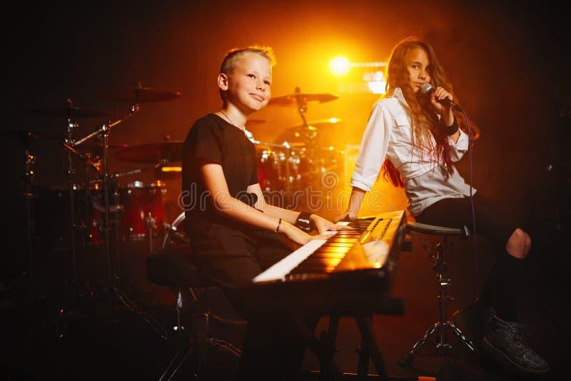 Kinder, die Musik im Tonstudio singen und spielen stockbilder