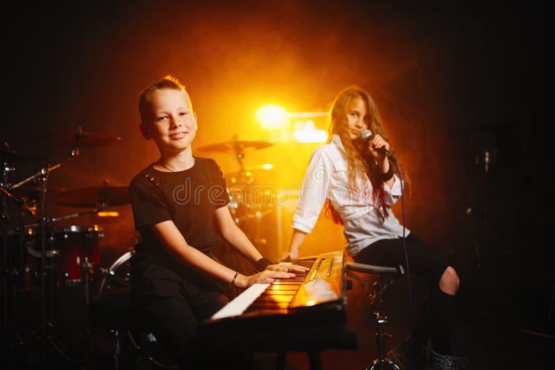 Kinder, die Musik im Tonstudio singen und spielen lizenzfreie stockbilder
