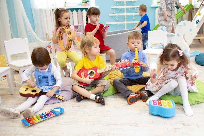 Kinder, die Musikinstrumente auf Lektion im Kindergarten oder in der Vorschule lernen lizenzfreie stockfotos
