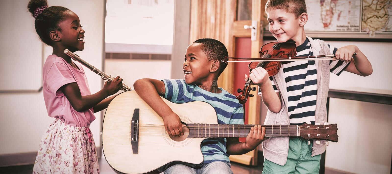Kinder, die Musikinstrumente im Klassenzimmer spielen stockfotos