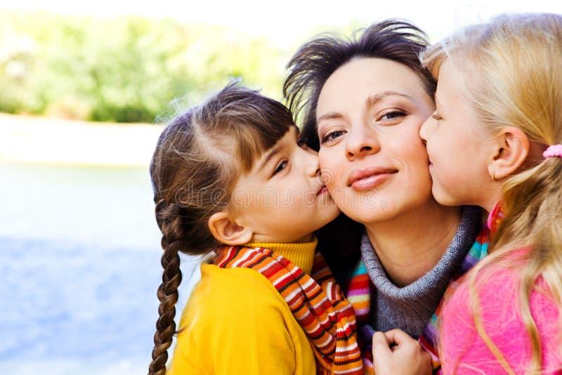 Kinder, die Mutter küssen stockfotografie