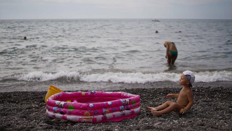 Kinder, die nahe aufblasbarem Babypool spielen Junge, der auf den Kieseln sitzt stockfotografie