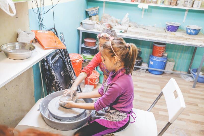 Kinder, die neue Fähigkeit an der Tonwaren-Werkstatt in Art Studio lernen stockbilder