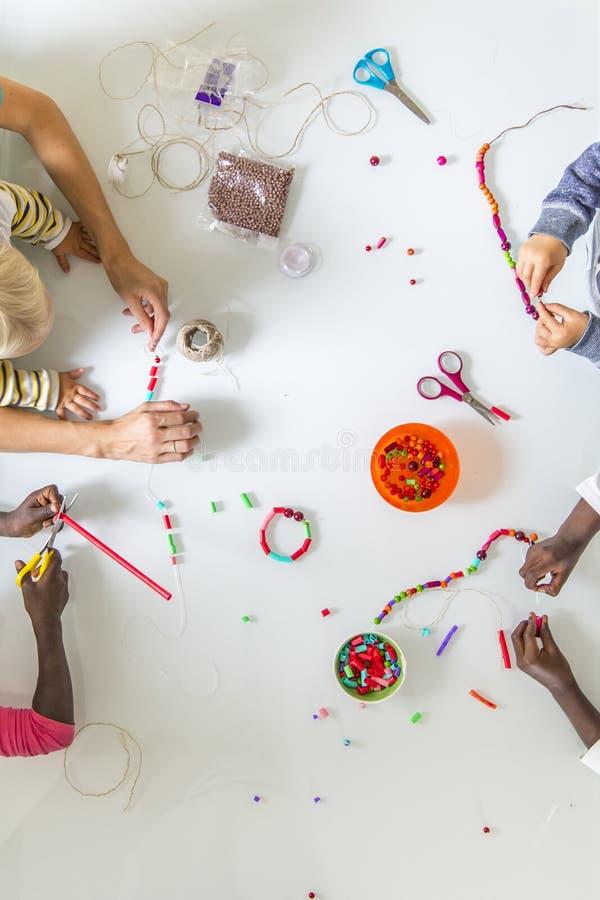 Kinder, die Perlenarbeit erledigen lizenzfreie stockfotografie