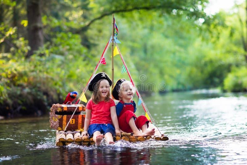 Kinder, die Piratenabenteuer auf hölzernem Floss spielen lizenzfreie stockfotografie