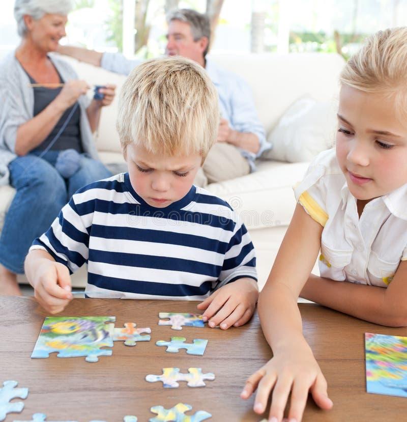 Kinder, die Puzzlespiel im Wohnzimmer spielen lizenzfreie stockfotografie