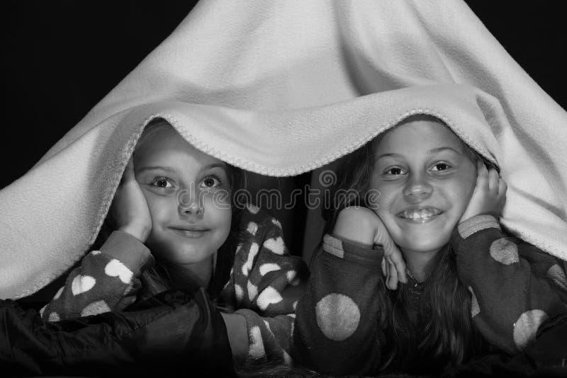 Kinder, die rote jammies im Bett auf schwarzem Hintergrund tragen stockfotos