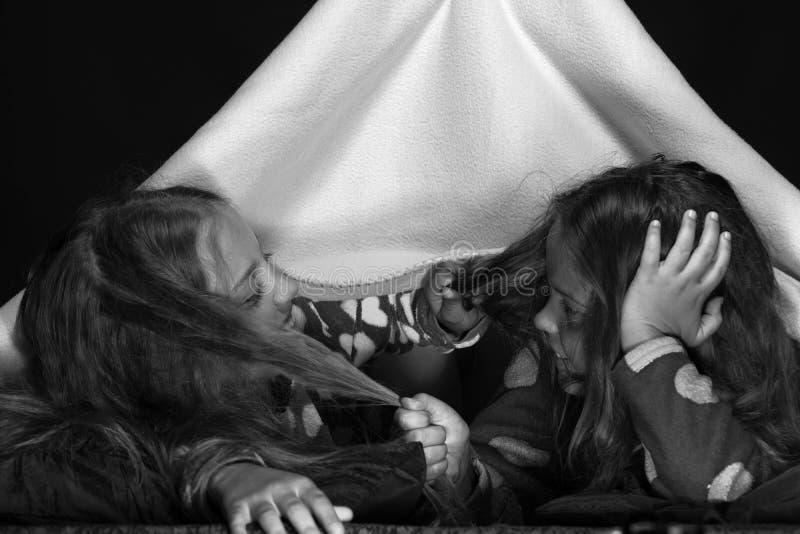 Kinder, die rote jammies im Bett auf schwarzem Hintergrund tragen Freundinnen unter der Decke, die auf jede andere Haar zieht stockfotos