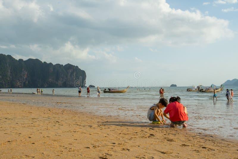 Kinder, die Sand spielen und einige Leute, die an Strand AO Nang vor dem Sonnenuntergang gehen und sich entspannen stockfotografie